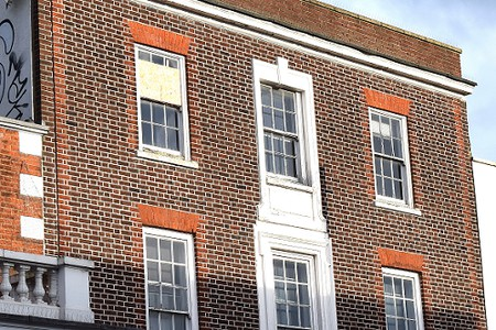 the upper windows of a red brick building with one window partly boarded up