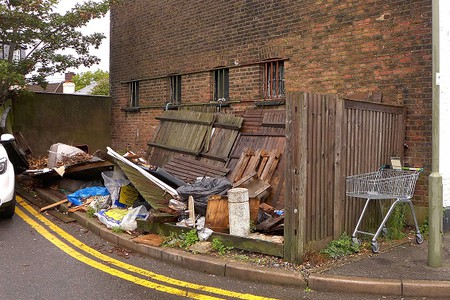 dumped fence panels and other rubbish at side of road