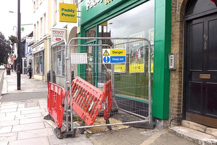 hole in the pavement with protective fencing round